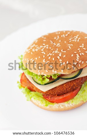 Junk food hamburger concept. Deep fried chicken or fish burger sandwich with lettuce, tomato, cheese and cucumber on white plate