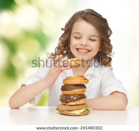 junk food, unhealthy eating, children and people concept happy smiling girl eating buns, donuts and burger over green background - stock photo