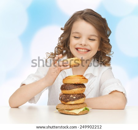 junk food, unhealthy eating, children and people concept happy smiling girl eating buns, donuts and burger over blue lights background - stock photo