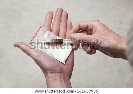 Junkie holding a dirty needle and the bag with cocaine - stock photo