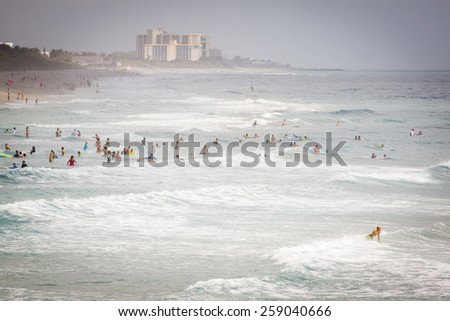 JUNO BEACH, FL - APRIL 20, 2013: Swimmers and surfers enjoy the ocean waves and warm weather at Juno Beach, Florida. - stock photo