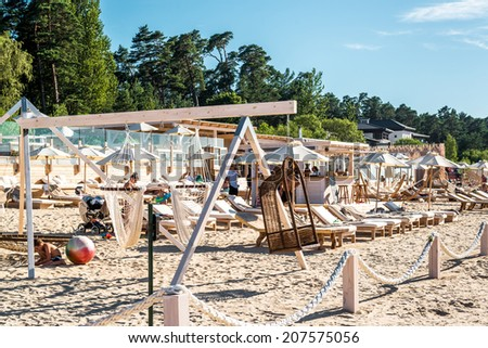 Jurmala, Latvia-July 19, 2014: People relaxing on Legend beach in resort town Jurmala, on a hot summer day, 30C outside on july 19, 2014
