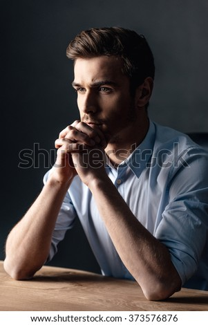 Just a moment to overthink everything. Side view of handsome young man keeping hands clasped and looking thoughtful while sitting against black background - stock photo