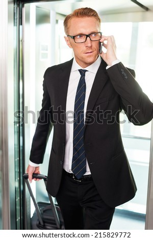 Just arrived. Confident young man in formalwear carrying suitcase and talking on the mobile phone while getting out of elevator - stock photo