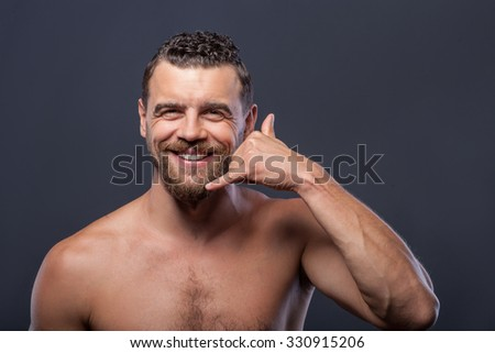 Just call me. Attractive young naked man is smiling and gesturing with his hand as if it is phone. He is standing and looking forward flirtingly. Isolated on grey background - stock photo