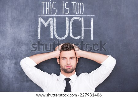 Just can not stand! Confused young man standing against chalkboard with hands on his head - stock photo