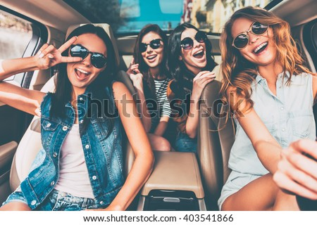 Just fun and road ahead. Four beautiful young cheerful women looking happy and playful while sitting in car - stock photo