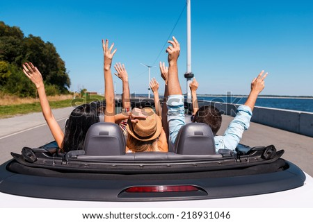 Just fun and road ahead. Rear view of young happy people enjoying road trip in their convertible and raising their arms up - stock photo