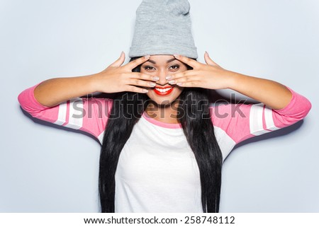 Just fun in my mind. Happy young African woman in funky clothes touching her face with fingers and smiling while standing against grey background  - stock photo