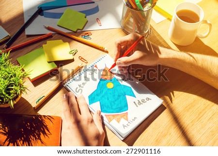 Just inspired. Close-up top view of man sketching on paper laying on the wooden desk - stock photo