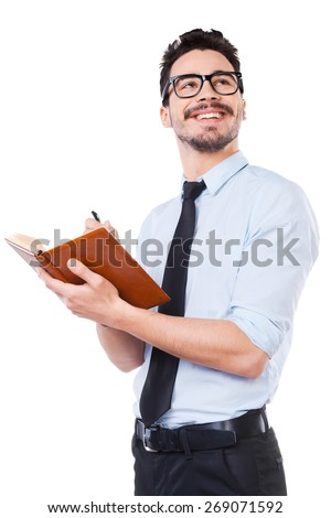 Just inspired. Low angle view of confident young man in shirt and tie making notes in his pad and smiling while standing against white background - stock photo