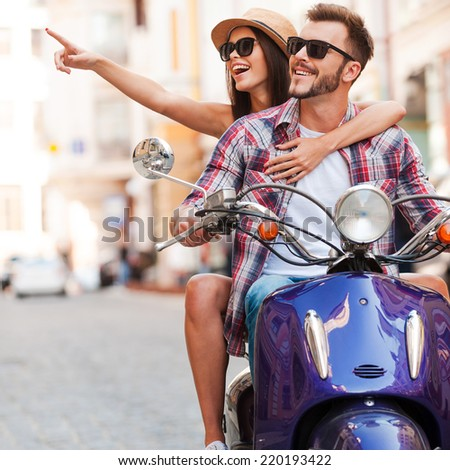Just look at that! Beautiful young couple riding scooter together while happy woman pointing away and smiling - stock photo