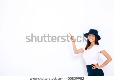 Just look at that! Beautiful young woman pointing up and smiling while standing against white background - stock photo
