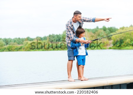 Just look at that! Father and son fishing together while standing on quayside together - stock photo