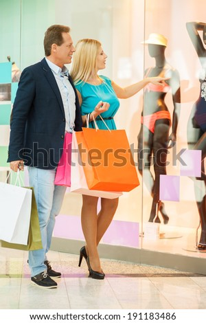 Just look at that! Full length of cheerful mature couple shopping in shopping mall while woman pointing mannequin