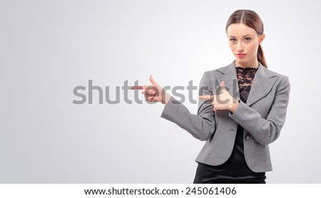 Just look at this! Confident young caucasian business woman pointing copy space while standing isolated on studio background - stock photo