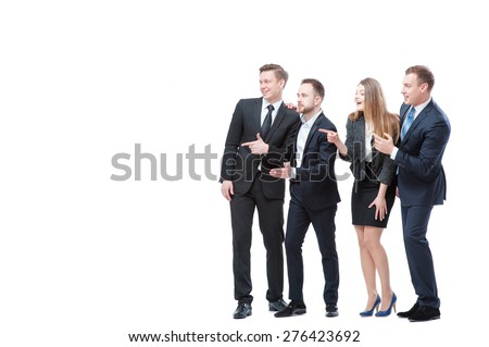Just look at this! Full length of group of surprised and amazed business people looking and pointing away. Isolated on white. - stock photo