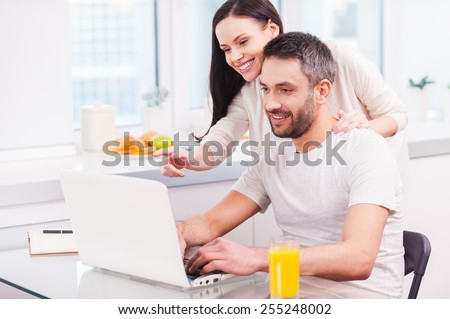 Just look at this! Handsome young man working on laptop and smiling while his cheerful girlfriend bonding to him and pointing monitor  - stock photo