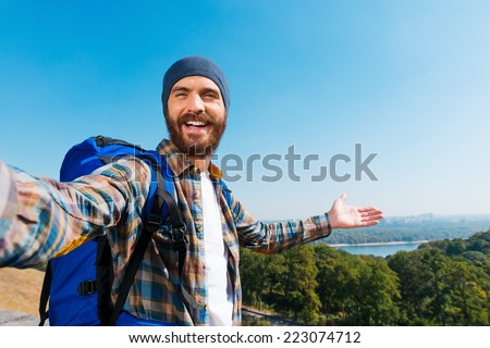 Just look! I am here! Handsome young man carrying backpack and taking a picture of himself and pointing to the view - stock photo