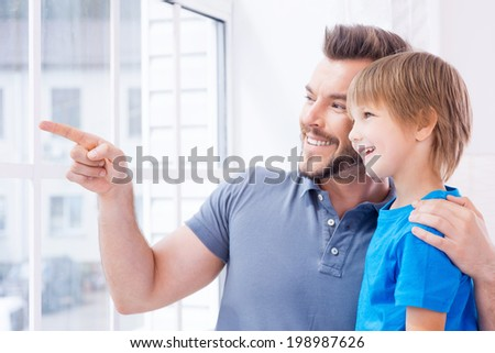 Just look over there! Happy father and son standing near the window while father pointing away and smiling - stock photo