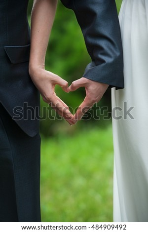 just married bride and groom hands making heart