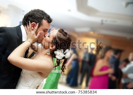 Just married couple dancing in front of their unrecognizable friends. - stock photo