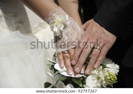 Just married couple hands with flowers.