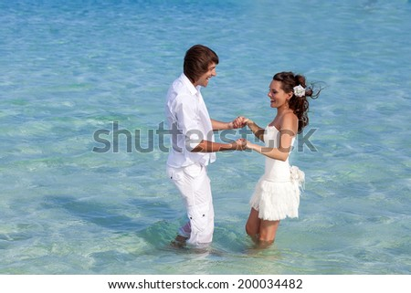 Just married couple is standing in the sea - stock photo