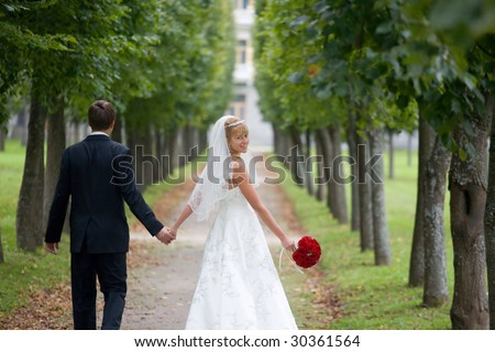 Just married couple is walking down the path in the park. The bride a wedding bouquet of red roses is turning back and smiling to the camera - stock photo