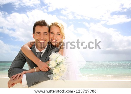 Just married couple leaning on fence by the beach - stock photo