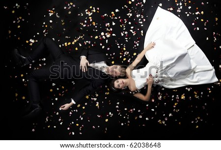 Just married couple lying on black backgruond with flower petals, a lot of copyspace available - stock photo