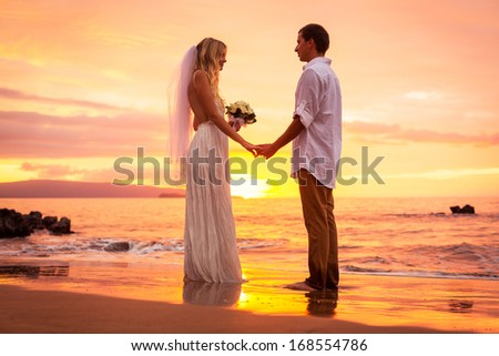 Just married couple on tropical beach at sunset, Intimate loving moment at wedding - stock photo