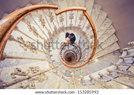 Just married couple together in a spiral staircase - stock photo
