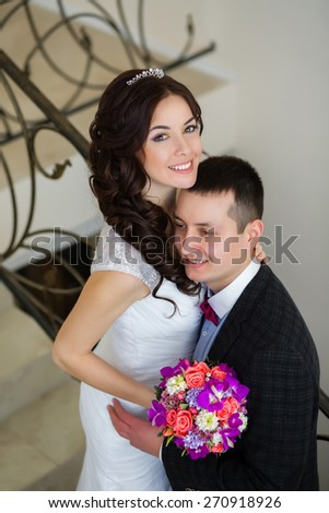Just married do embrace on the stairs  - stock photo