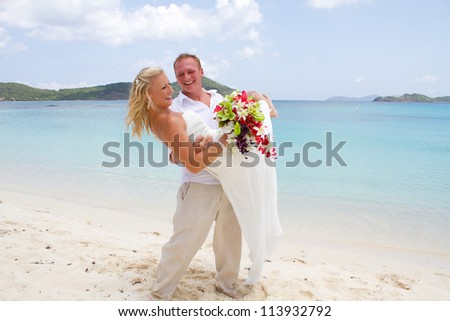 Just married groom carrying bride on tropical beach