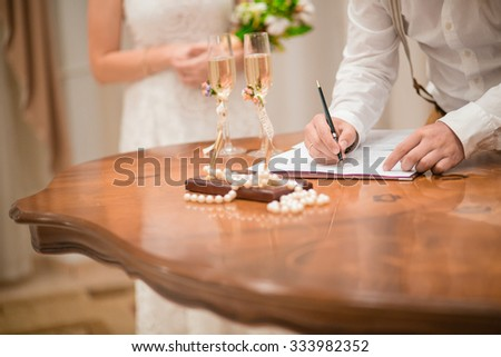 Just married in the registry office, the groom puts his signature on the document, wedding day - stock photo