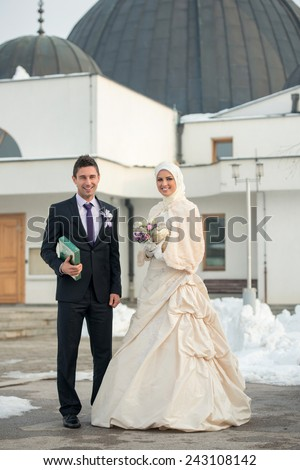 Just married muslim couple posing in front of mosque - stock photo