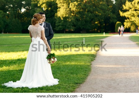 Just married romantic couple walking in the park at sunset. Bride kissing and hugging groom