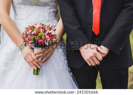 Just married standing side by side. Bride holding bouquet. - stock photo