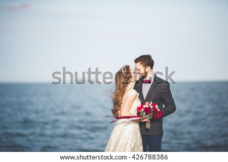 Just married wedding couple walking on the beach at sunset. - stock photo