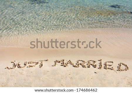 Just Married written in sand on a beautiful beach, blue clear waves in background - stock photo