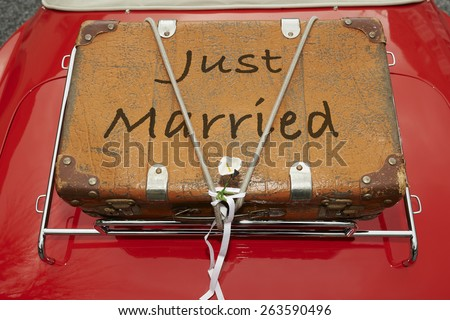 Just Married written on a suitcase placed on the trunk of a red car - stock photo