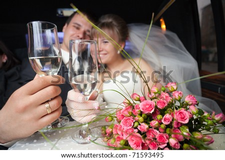 Just married young couple inside limo with flowers and champagne - stock photo