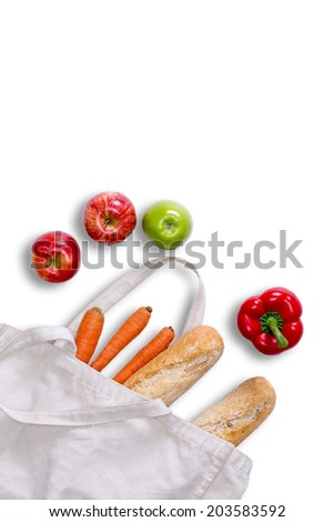Just returned from grocery shopping concept with a white tote bag lying on its side with fresh baguettes carrots red bell peppers and red and green apples spilling onto a white surface view from above - stock photo
