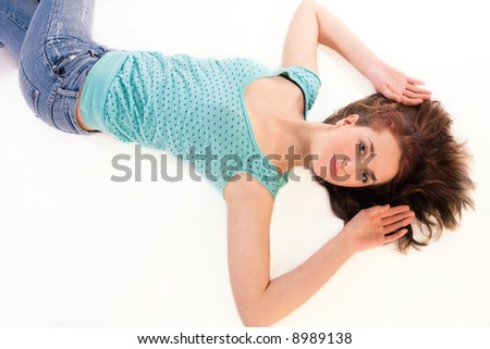 just seventeen, a coy teenager with red brown hair lying down - stock photo