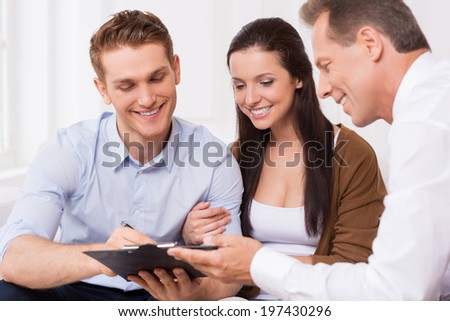 Just sign here. Happy young couple signing documents while confident mature man holding clipboard and smiling   - stock photo