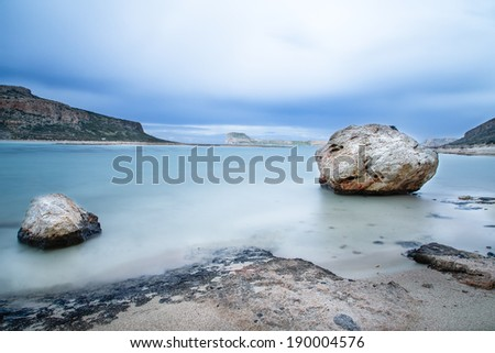Just the two of us - two rocks standing in shallow water on a deserted tropical beach on Crete, Greece with rocky cliffs in the distance across the bay, scenic background long exposure image - stock photo