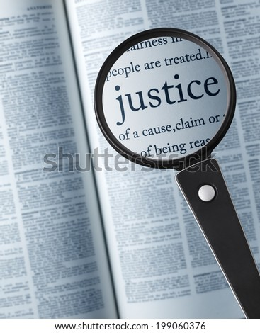 """justice/Magnifying glass on the""""justice"""" in dictionary - stock photo"""