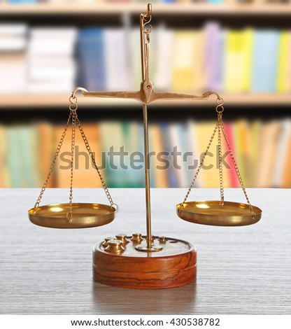 Justice scales on table in library