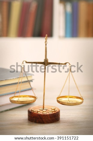 Justice scales with stack of books on wooden table